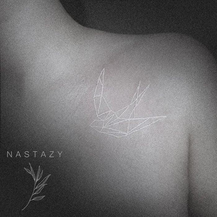 Tatuaje de una golondrina de origami en tinta blanca sobre el hombro