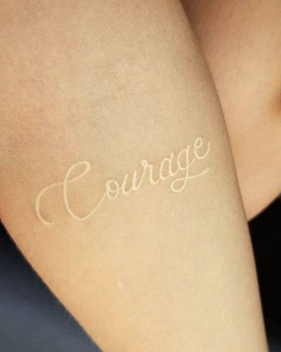 Tatuaje de tinta blanca con la palabra courage escrita en el brazo