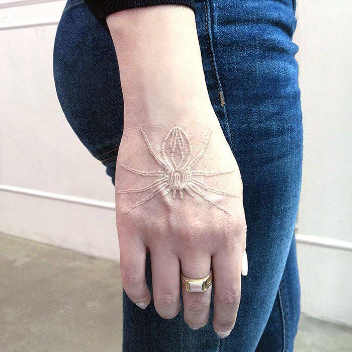 Diseño de tatuaje de tinta blanca en forma de araña en la mano