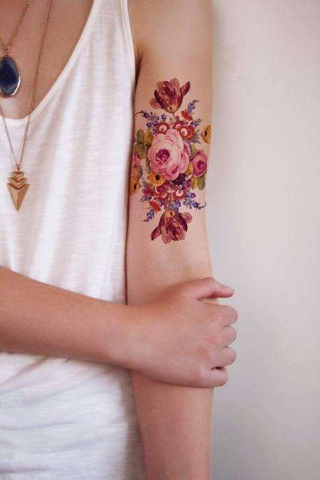 Mujer con tatuaje realista de flores en el brazo