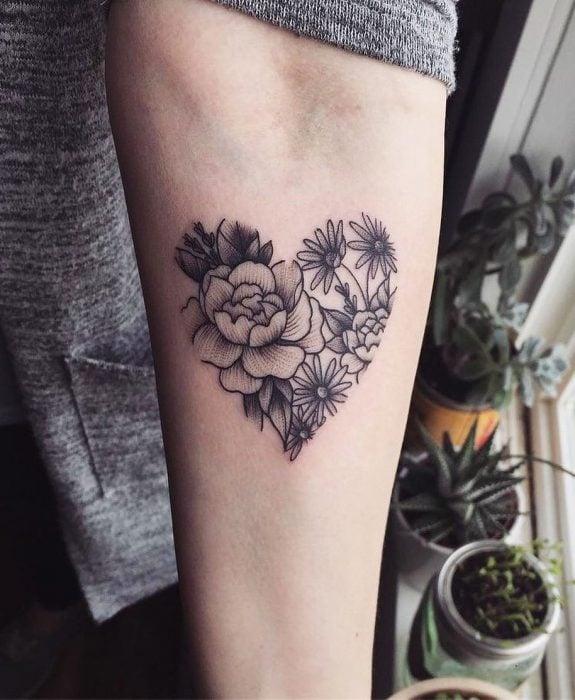 Mujer con tatuaje de flor en el brazo
