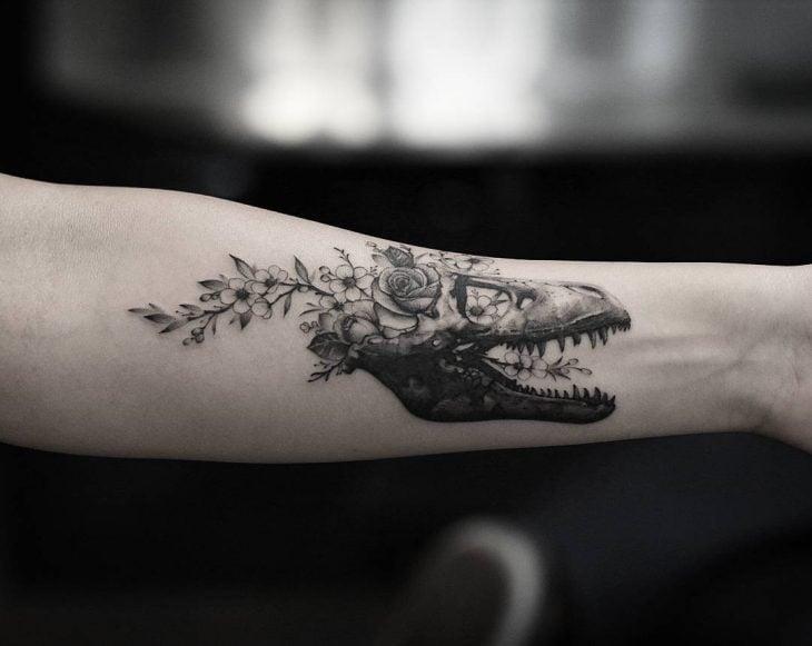 Mujer con tatuaje de flor y cráneo en el brazo
