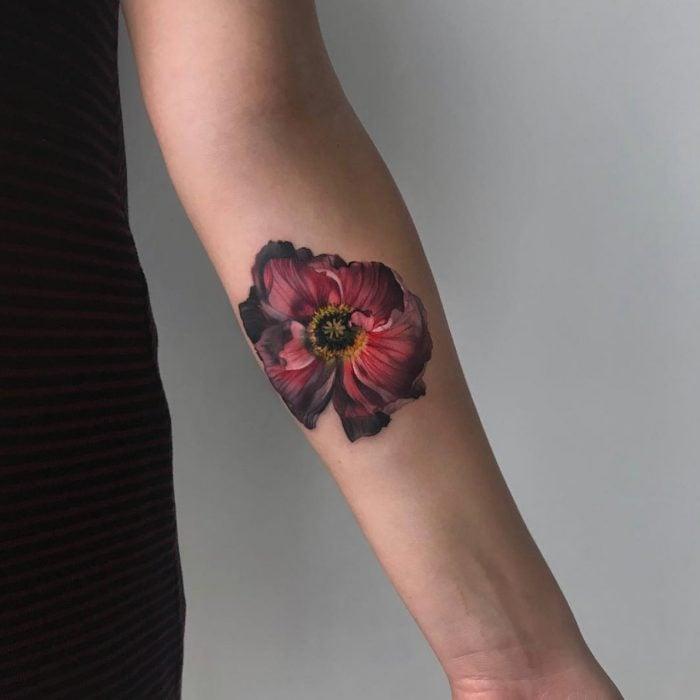 Mujer con tatuaje de flor roja realista en el brazo