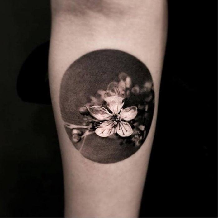 Mujer con tatuaje de flor realista en el brazo