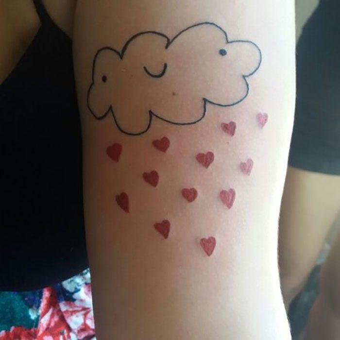 Tatuaje en el brazo mal hecho y feo de una nube sonriente que arroja lluvia de corazones