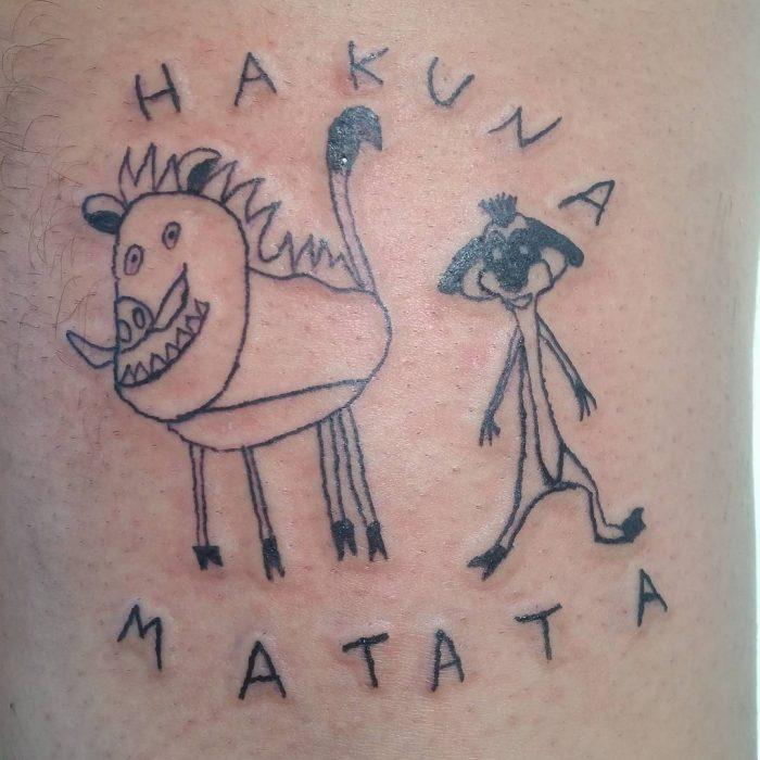 Tatuaje como dibujo infantil de Timón y Pumba del Rey León con la frase Hakuna Matata hecho por la tatuadora Helen Fernandes