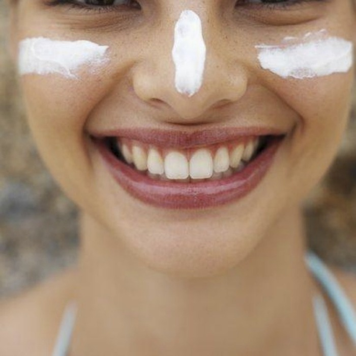 chica sonriendo, usando protector solar en su nariz y mejillas