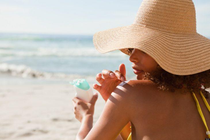 Chica en la playa usand sombrero amplio, aplicando protector solar sobre su hombro