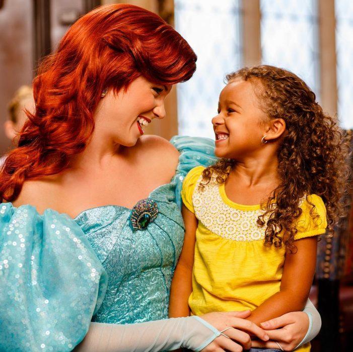 Mujer vestida de Ariel de la Sirenita con una niña sentada en sus piernas mientras ambas sonríen