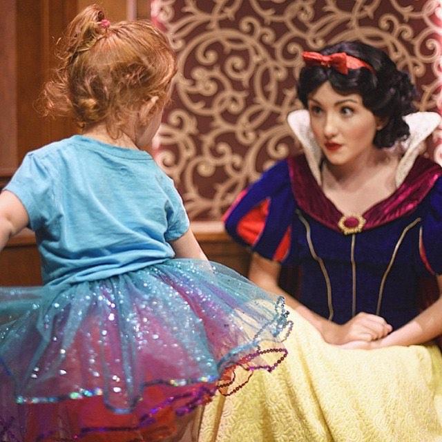 Chica vestida de Blancanieves mirando de forma sorprendida a una niña que está vestida con playera y un tutu