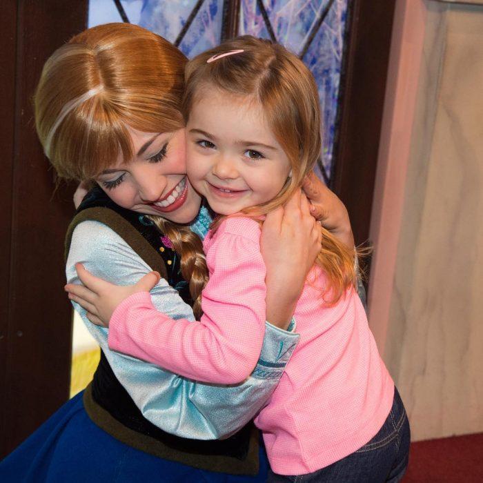 Chica vestida de Anna de la película de Frozen abrazando a una niña en Disneyland