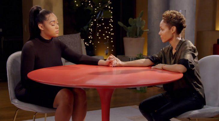 Jordyn Woods tomando de la mano a Jada Pinkett Smith mientras ambas están sentadas conversando en una mesa roja para el programa Red Table Talk