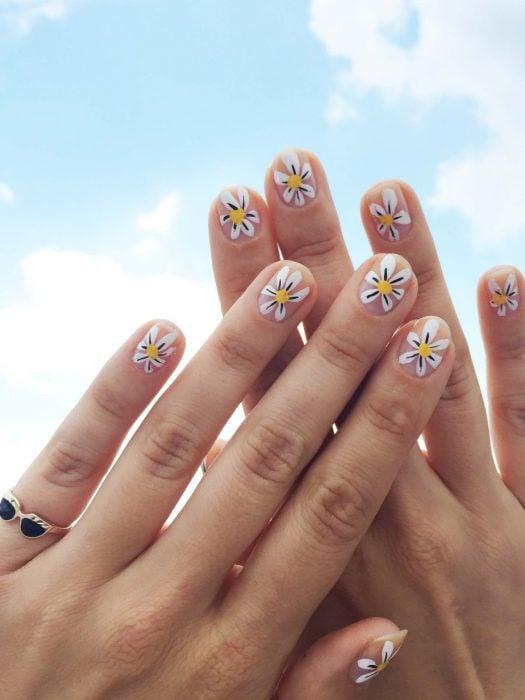 Mano de mujer con uñas con simples flores blancas pintadas que puedes hacer en tu casa para recibir la primavera. anillo de lentes