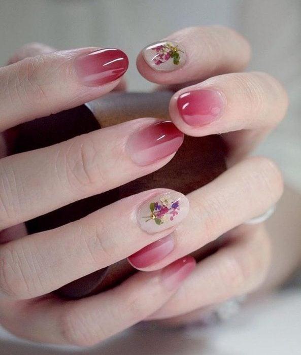 Manos de mujer con uñas pintadas con esmalte rosa degradado y pequeñas flores blancas, rosas y moradas con una piedra dorada