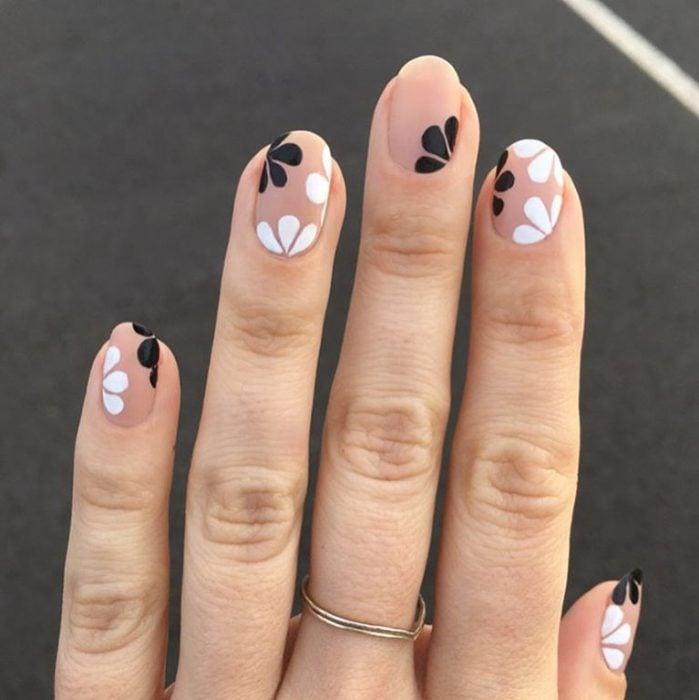 Mano de mujer con anillo dorado y uñas color carne adornadas con flores minimalistas y sencillas de color blanco y negro para la primavera