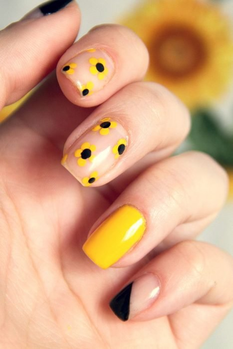 Mano me mujer con uñas pintadas de color amarillo y negro con flores sencillas para primavera