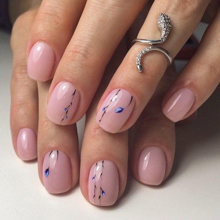 Manos de mujer con anillo plateado de serpiente con diamantes y uñas pintadas de rosa pálido con flores azules sencillas para la primavera