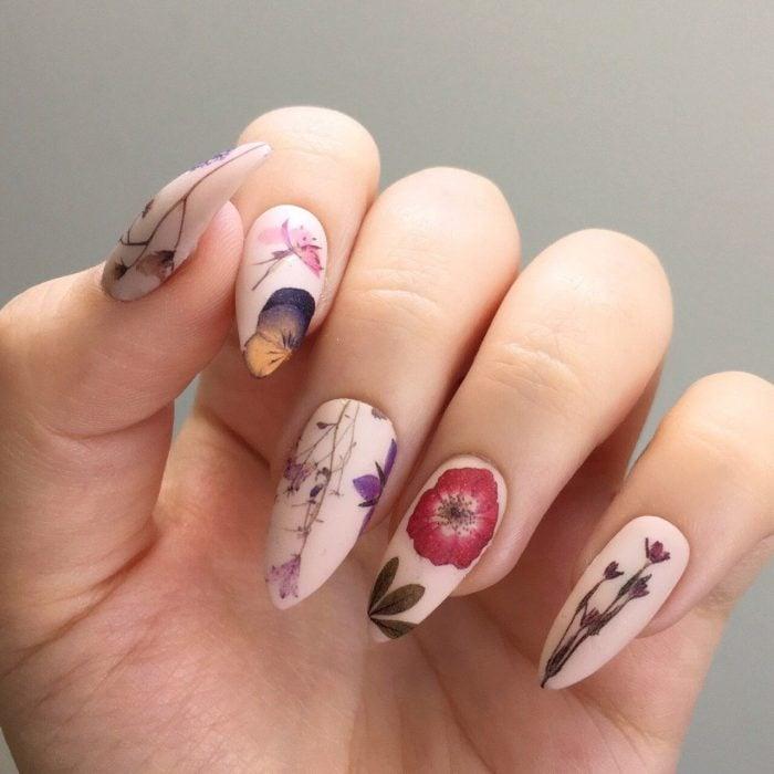 Mano de mujer con uñas largas con flores realistas pintadas de diferentes colores sobre una base rosa pálido mate para la primavera