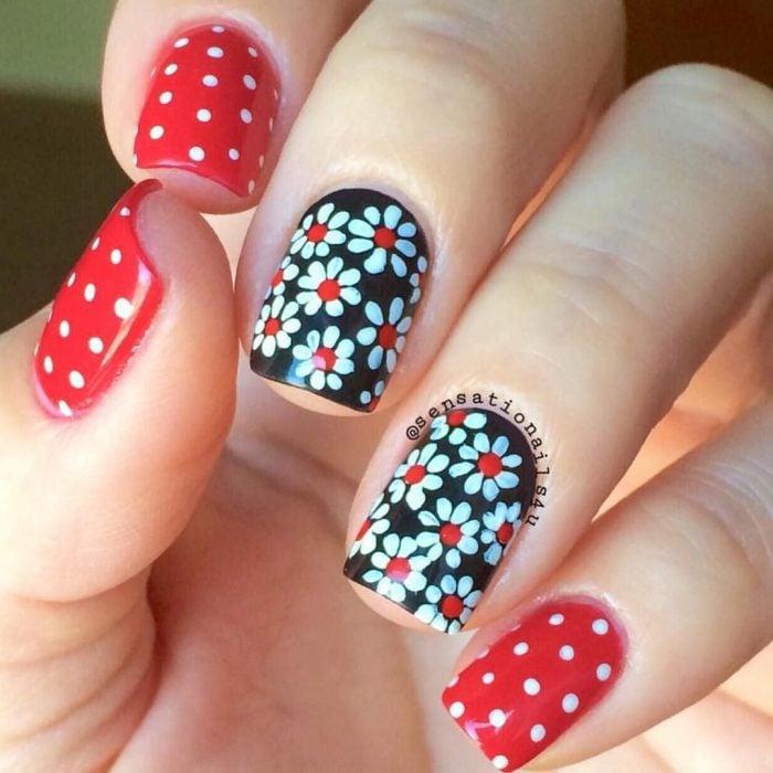 Mano de mujer con uñas pintadas de color negro y rojo, con estampado de flores y puntos blancos para la primavera