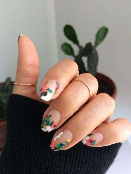Mano de mujer con uñas con flores coloridas, verde, rosa y blanco mate, sencillas pintadas sobre base transparente para primavera, anillos dorados