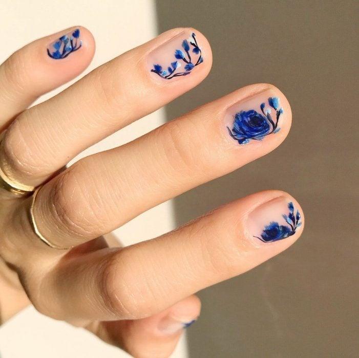 Mano de mujer con anillos dorados y uñas pintadas con flores azul rey sobre esmalte transparente