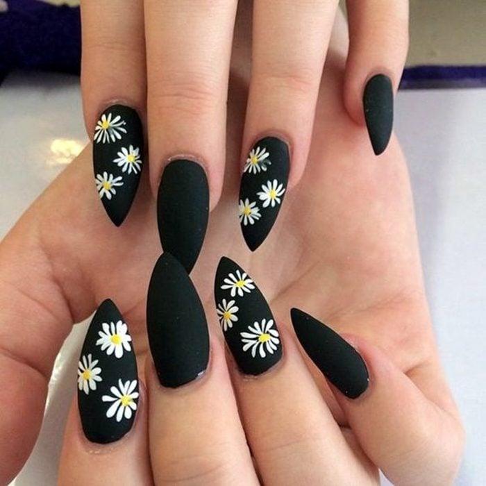 Mano de mujer con uñas largas en forma de almendra pintadas de negro mate con flores margaritas para la primavera