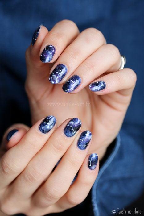 Manicura femenina de constelaciones, uñas con esmalte azul de universo con estrellas