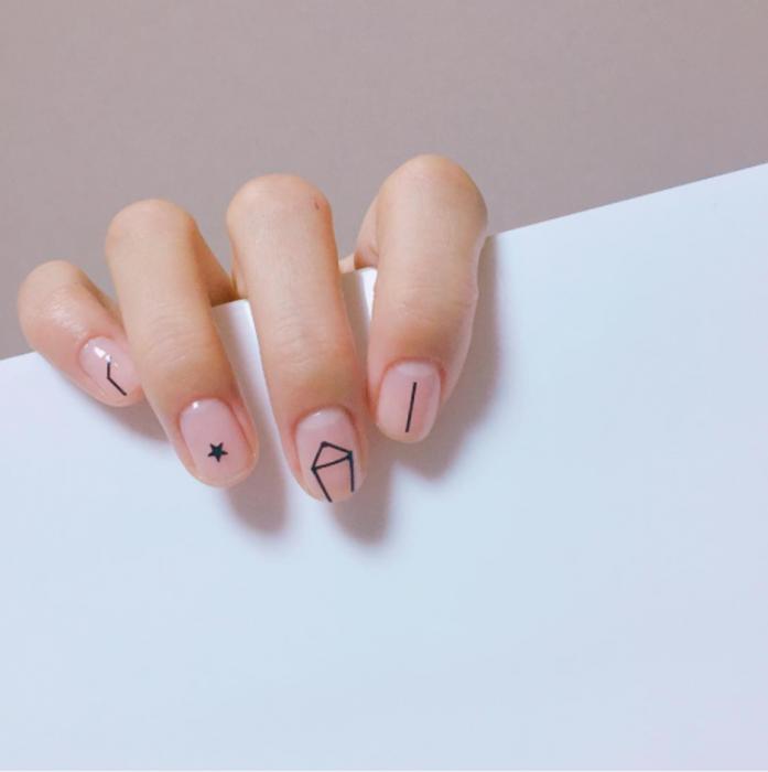 Manicura femenina y minimalista de consteñaciones con esmalte transparente y estrellas negras