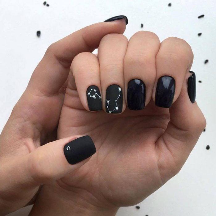Manicura rockera y femenina de constelaciones con esmalte negro brillante y mate, y estrellas blancas