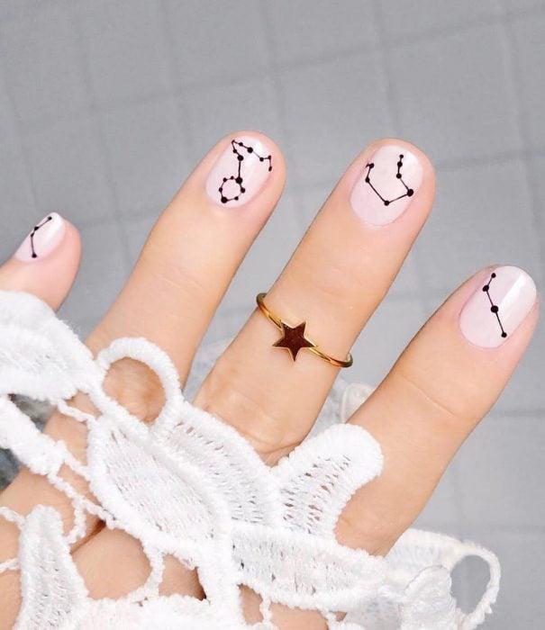 Manicura femenina y minimalista de constelaciones con esmalte color perla y estrellas negras con un anillo dorado de estrella