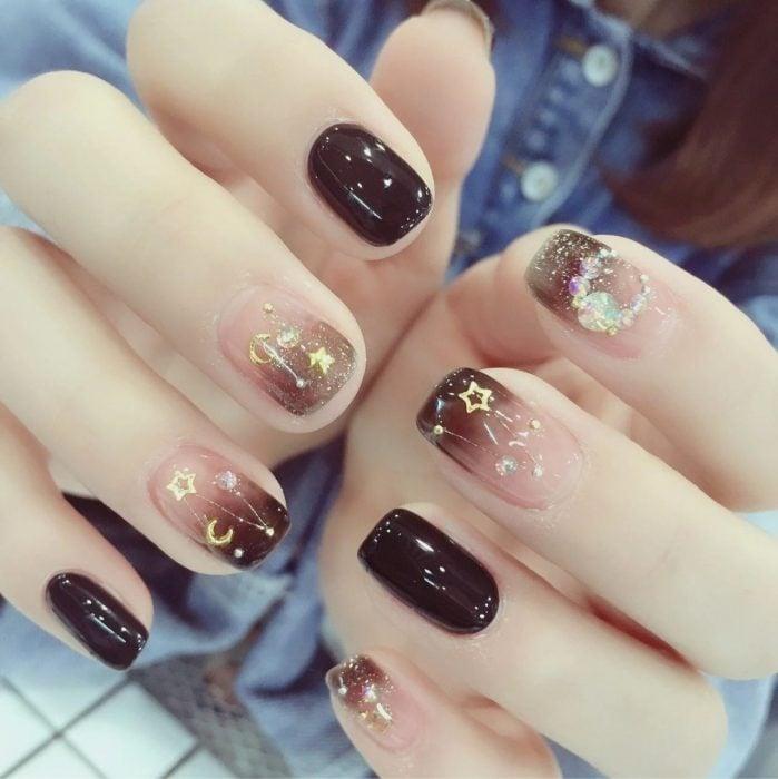 Manicura femenina de constelaciones con esmalte color café sólido y degradado, estrellas doradas y pedrería de fantasía