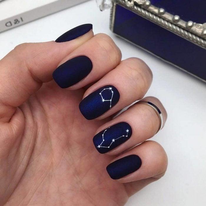 Manicura femenina y minimalista de constelaciones, uñas con esmalte color azul rey y estrellas