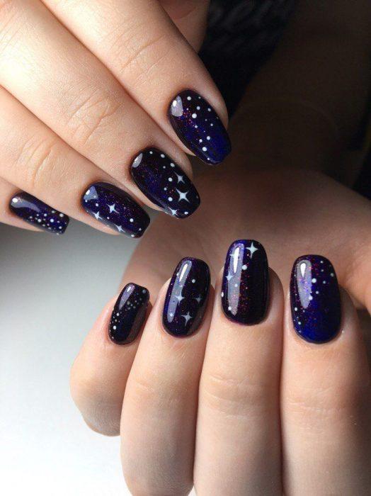Manicura femenina de constelaciones con esmalte color azul marino con brillos y estrellas blancas