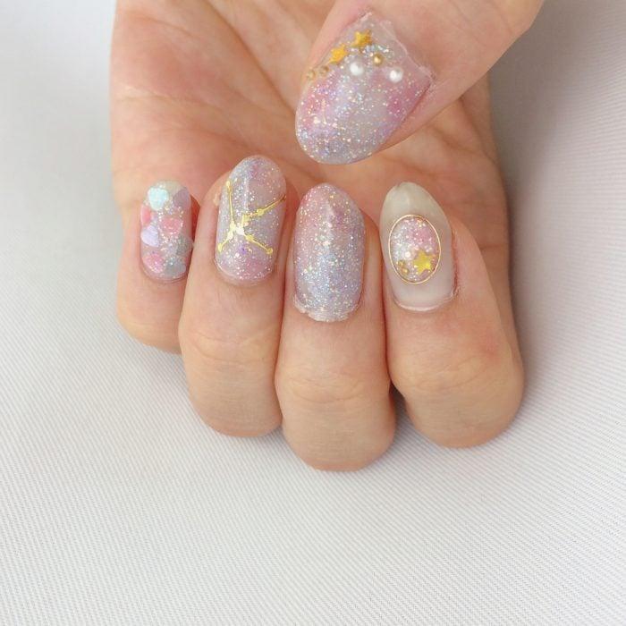 Manicura femenina de constelaciones con esmalte rosa con brillos, estrellas doradas, corazones y cuentas blancas