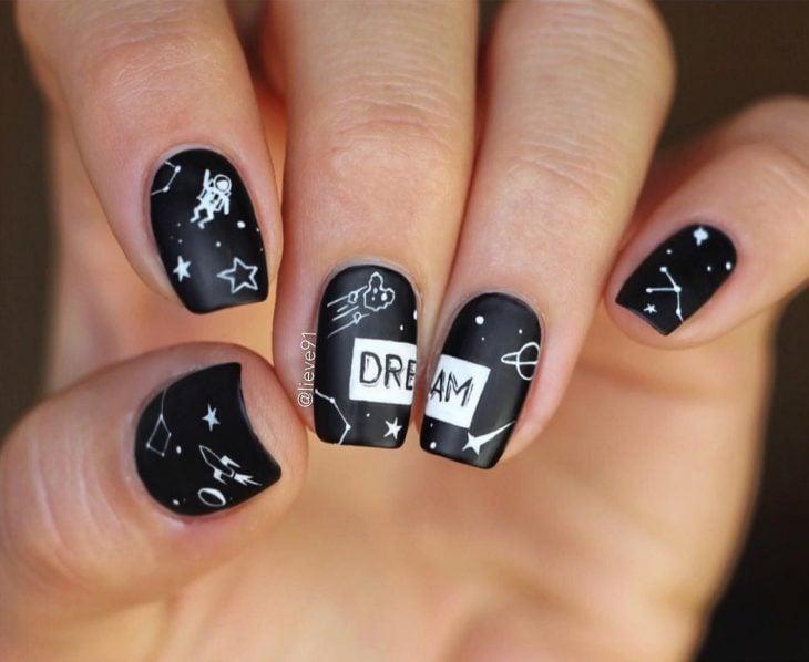 Manicura creativa y divertida de constelaciones, con esmalte negro y estrellas, cohetes, ateroides y astronauta blancos