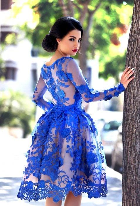 Chica de cabello negro con peinado de chongo recargada en un árbol con vestido de fiesta corto color azul royal con encaje de flores y transparencias, maquillaje de fiesta