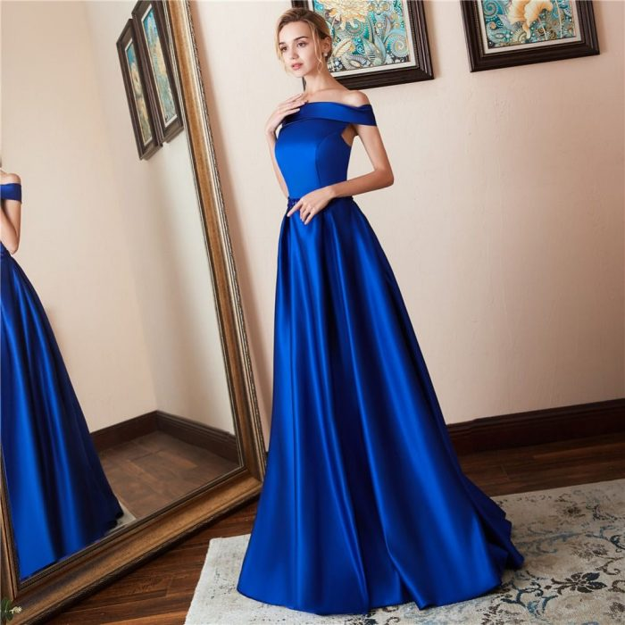 Chica rubia frente al espejo con vestido de fiesta largo color azul royal satinado sin hombros