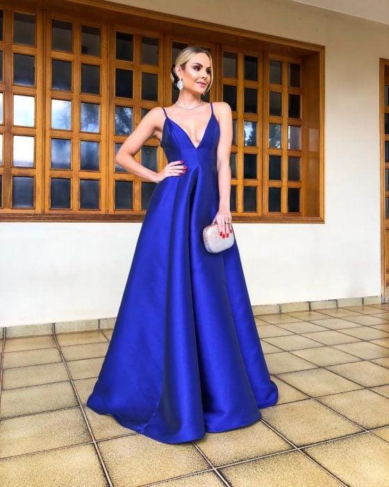 Mujer rubia con peinado de chongo usa vestido largo de fiesta color azul royal satinado con escote en v y tirantes, bolsa de mano brillante
