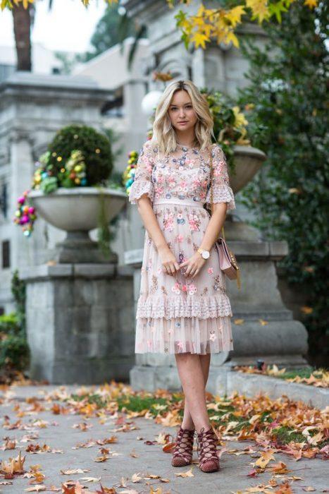 chica con la pierna cruzada con vestido rosa de encaje estilo boho
