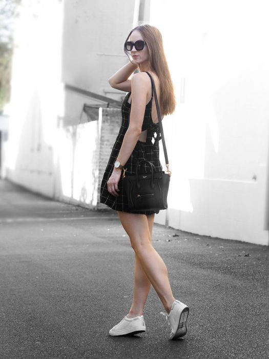 chica caminando por la acera con tenis blancos y vestido negro corto