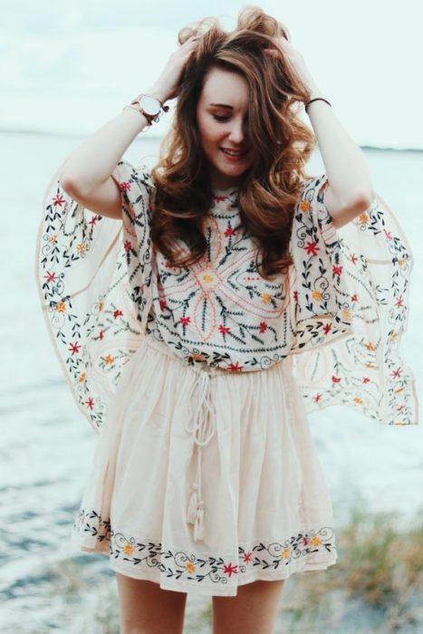 chica acariciando su cabello en vestido corto de encaje estilo boho
