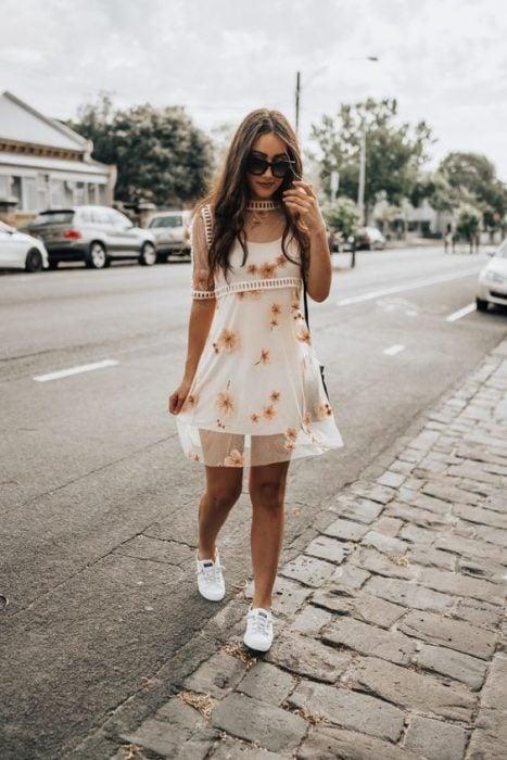chica llevando tenis con vestido blanco con gasa encima