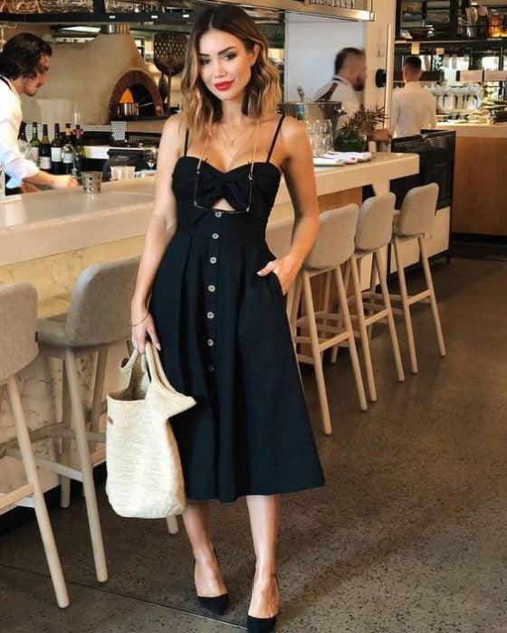 chica dentro de un restaurante con vestido oscuro largo