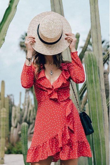 chica cubriendo su rostro con un sombrero con vestido corto rojo con lunares blancos y holanes