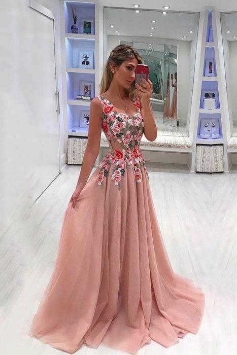 Chica tomándose una fotográfica con su celular, modelando un vestido rosa transparente con detalles de flores