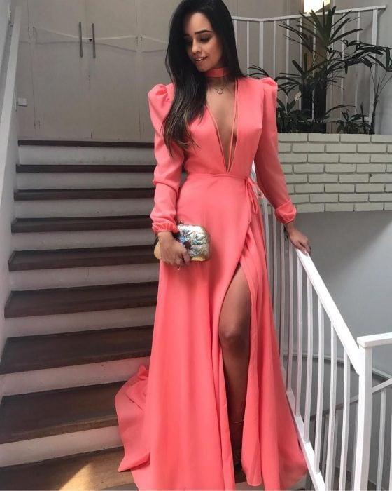 Chica sobre unas escalera modelando un vestido color salmón con bolso plateado en mano