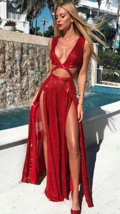 Chica en la calle modelando un vestido color rojo, con aberturas en ambas piernas y escote