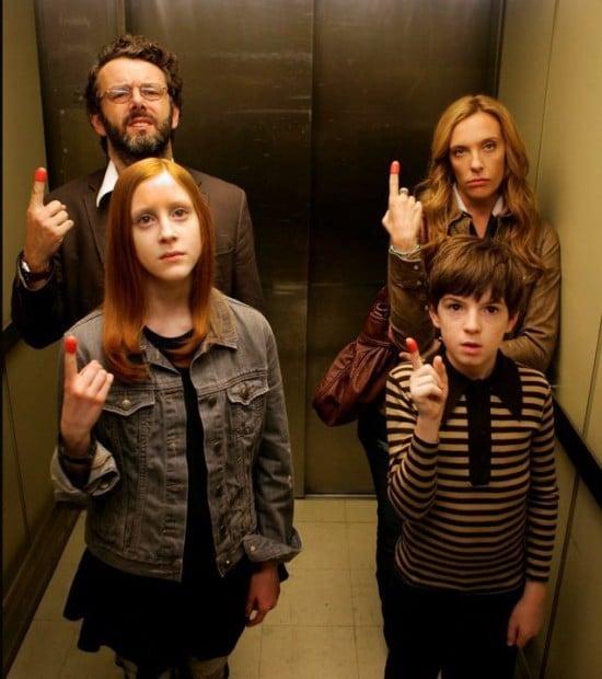 familia dentro de un elevador enseñando dedo índice con la punta roja