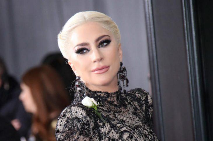 Lady Gaga modelando en la alfombra roja con vestido de encaje en negro