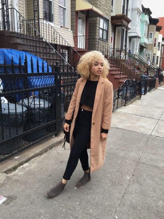 Chica camina sobre la calle, con traje negro y un saco café camel